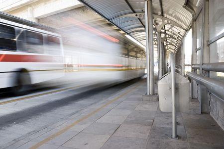 fermata bus: Deserted fermata con il bus accelerare passato e spazzatura in primo piano. Motion offuscata colpo.