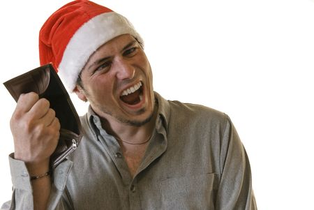 empty wallet: Angry young man with Santa hat holding an empty wallet and making barking mad face. White background. Stock Photo