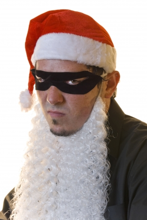 Young man wearing Santa red hat and beard with bandit mask, frowning. White background. Stock Photo