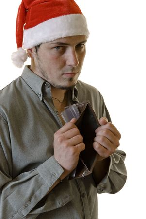 empty wallet: Young man wearing a red Santa hat and holding an empty wallet, making slightly sad face. White background. Stock Photo