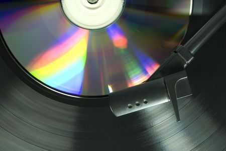 Cropped image shot directly from above of a record player needle, with LP  and CD underneath