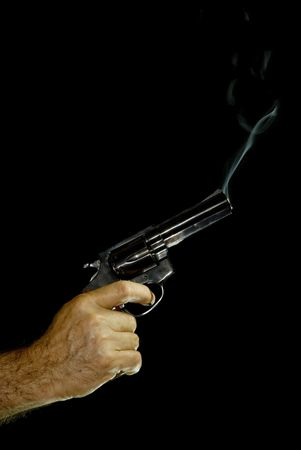 Male hand holding a .38 caliber revolver, with bluish smoke coming out of it. Black Background.