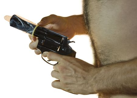 38 caliber: Cropped shot of a male hand holding a .38 caliber with a condom on it and hairy chest from the side. White background.