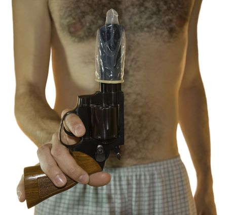 Cropped shot of a male hand holding a .38 calibre with a condom on it and hairy chest in the background. Front shot with white background.
