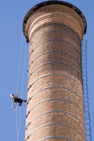 cropped shot: Cropped shot of an unrecognizable workers hanging from a high industrial brick chimney. Blue sky in the background. Stock Photo