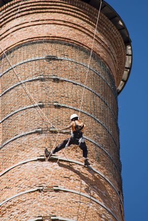 Cropped shot of an unrecognizable workers hanging from a high industrial brick chimney. Blue sky in the background. Stock Photo