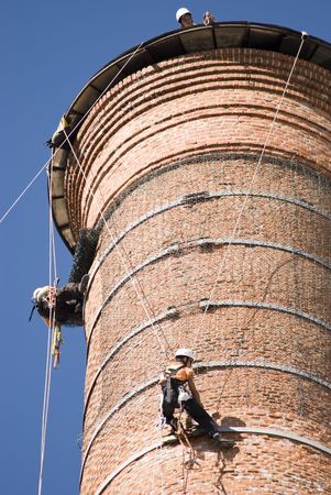 Cropped shot of two unrecognizable workers hanging from a high industrial brick chimney. Blue sky in the background.