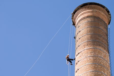 Cropped shot of an unrecognizable workers hanging from a high industrial brick chimney. Blue sky in the background, with huge copy space.
