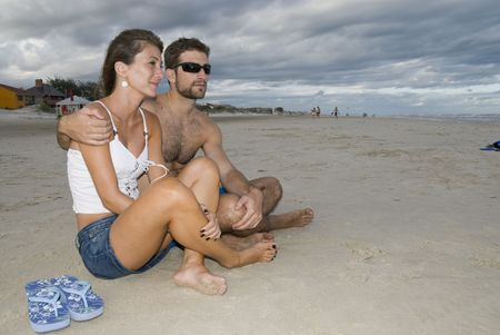 sitted: Young healthy couple sitted in the sand, looking out into the sea (side shot).