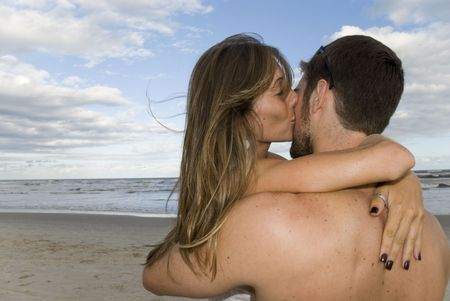Young healthy couple kissing in the beach.