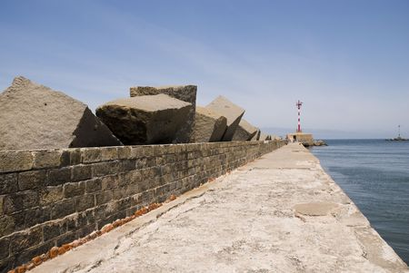 Perspective shot of pier in Montevideo, with small lighthouse in its end