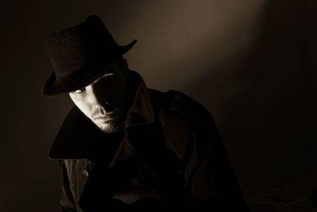 dodgy: Sepia toned noir portrait of suspicious looking young man. Harsh highlights and shadows.