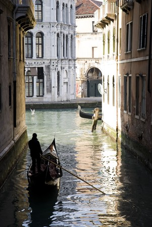 Gondolier rowing through waterway in Venice, Italy Stock Photo