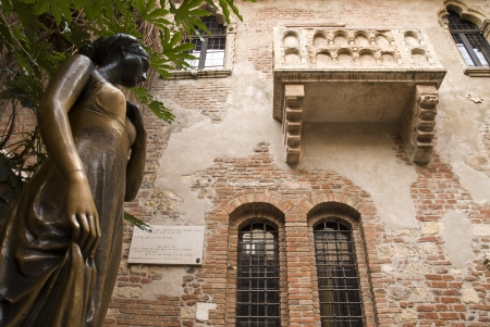 Low angle shot of statue of Juliet, with balcony in the background.