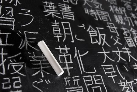 Chalk on blackboard filled with Chinese and Japanese characters. The words in Japanese have random meanings.