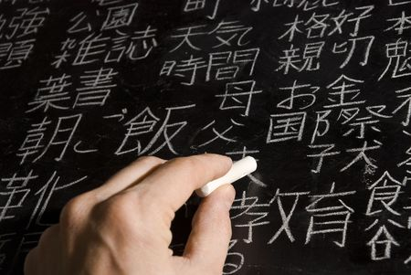 japanese symbol: Close up of male hand writing Chinese and Japanese characters on blackboard. The words in Japanese have random meanings.