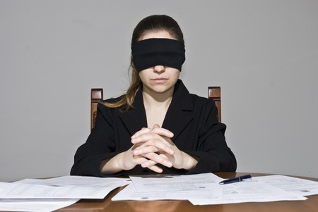 Blindfolded businesswoman signing papers photo
