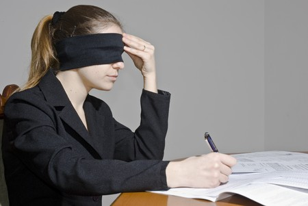 blindfolded: Blindfolded businesswoman signing papers