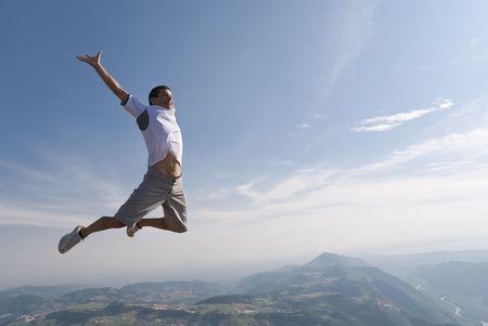 El hombre joven y sano saltando en el aire con el fondo de montaña y un montón de espacio de la copia.
