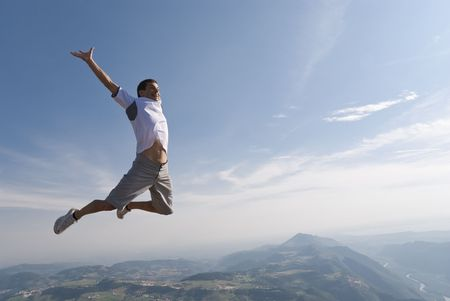 Healthy young man jumping in mid-air with beautiful mountain background and lots of copy space.