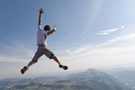midair: Healthy young man jumping in mid-air with beautiful mountain background and lots of copy space.