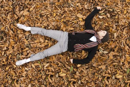High angle full body shot of young man laying on the yellow leaves covered ground. Stock Photo - 5897849