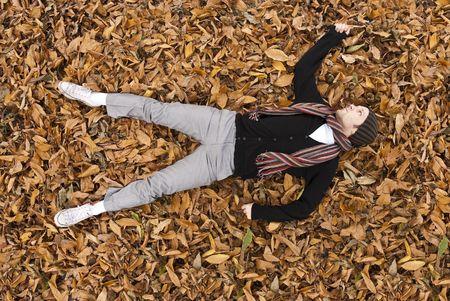 full body shot: Chupito de cuerpo completo de �ngulo alto de hombre joven puesta sobre el terreno de hojas amarillas cubiertas.