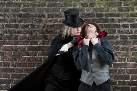 Fashion shot of woman  dressed as Jack the Ripper strangling man Stock Photo