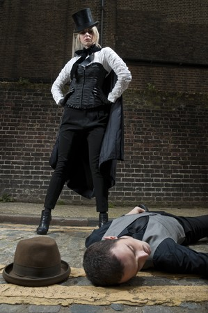 british man: Woman dressed as Jack the Ripper on top of man lying on the ground. Stock Photo