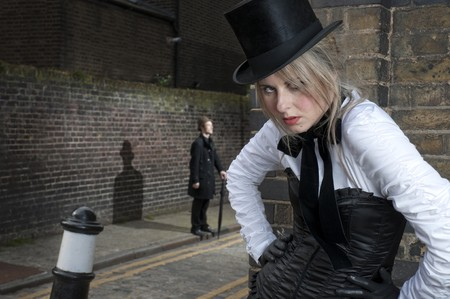 Street Fashion shot of woman in late victorian clothes with man in the background. photo