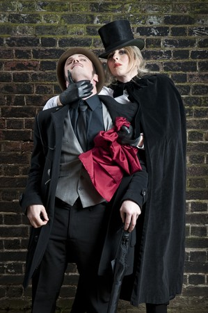 Fashion shot of woman  dressed as Jack the Ripper stealing mans handkerchief.