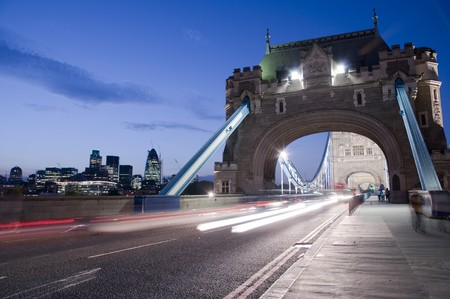 Detail of Tower Bridge in London at dusk with car light trail and city in the background. Stock Photo