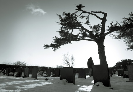 Lonely figure standing amongst tombstones in snowy cemetery. photo