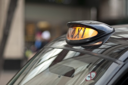 cab: Close up of a London black cab with yellow light on.