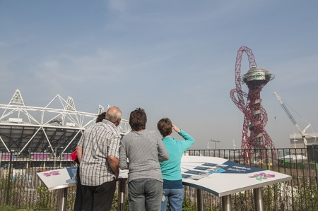 anish: LONDON, UK � MARCH 24: Visitors looking at Olympic Stadium and Anish Kapoor sculpture in the background on March 24, 2012 in London. The Olympic Park is due to be ready in summer.