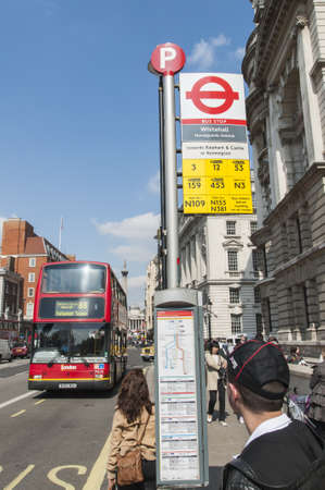 LONDON, UK - APRIL 02: Bus stop with red double-decker bus approaching and commuters waiting. April 02, 2012 in London.