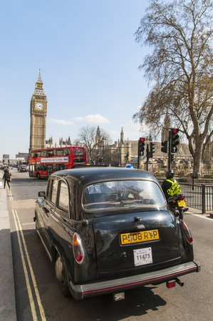 LONDON, UK - APRIL 02: Famous black cab driving by Houses of Parliament, with Big Ben prominent in the picture. April 02, 2012 in London. Stock Photo - 13062870