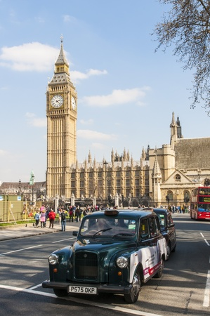 LONDON, UK - APRIL 02: Famous black cab driving by Houses of Parliament, with Big Ben prominent in the picture. April 02, 2012 in London.