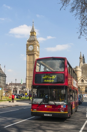 route master bus: LONDON, UK - APRIL 02: Famous red double-decker bus driving by Houses of Parliament, with Big Ben prominent in the picture. April 02, 2012 in London.