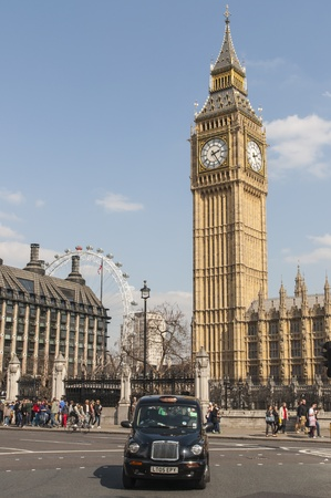 LONDON, UK - APRIL 02: Famous black cab driving by Houses of Parliament, with Big Ben prominent in the picture. April 02, 2012 in London. Stock Photo - 13062860