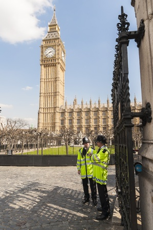 LONDON, UK - APRIL 02: Two policemen guard the front entrance to the Houses of Parliament, with Big Ben prominent in the picture. April 02, 2012 in London.