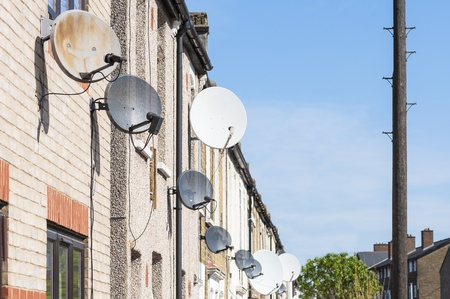 Row of satellite dishes installed in front of brick houses. Stock Photo - 13294078
