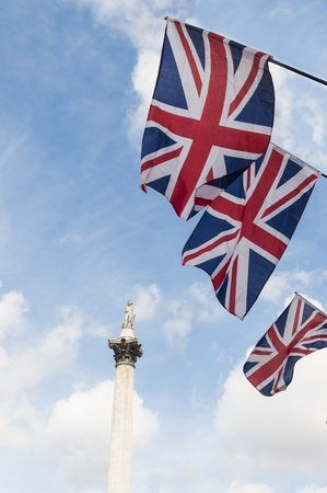 British Union flags in row, with Nelson column in background. photo