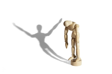Sad wooden mannequin with happy shadow isolated in white background. Stock Photo