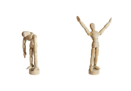 Two wooden mannequins, one celebrating and the other sad, against white background. Stock Photo