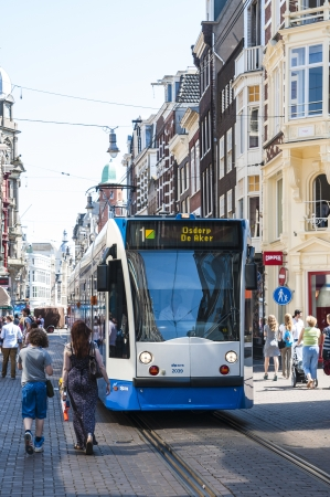 kilometres: AMSTERDAM, HOLLAND - MAY 27: Tram running in the city centre amongst pedestrians. May 27, 2012 in Amsterdam. The tram network comprises 16 lines and covers 213 kilometres.