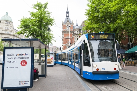 kilometres: AMSTERDAM, HOLLAND - MAY 29: Tram running in the city centre amongst pedestrians. May 29, 2012 in Amsterdam. The tram network comprises 16 lines and covers 213 kilometres. Editorial