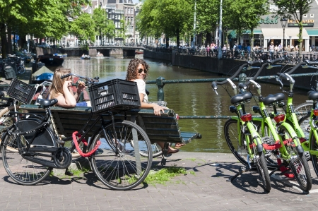 AMSTERDAM, HOLLAND - MAY 27: Dutch people sitting close to busy bicycle parking lot in the city centre. May 27, 2012 in Amsterdam. It is estimated that there are about 550 thousand bikes in Amsterdam.