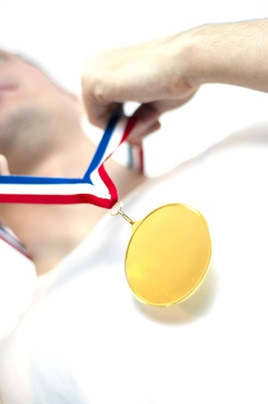 Cropped low angle shot of man wearing blank sports gold medal. Stock Photo