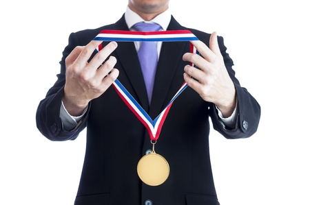gold medal: Cropped torso of man wearing black suit and awarding blank sports gold medal. Stock Photo